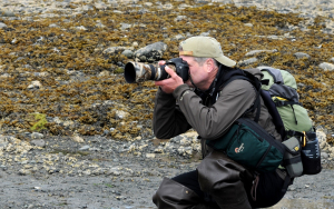 Man pointing camera at something out of frame while wearing hiking gear.