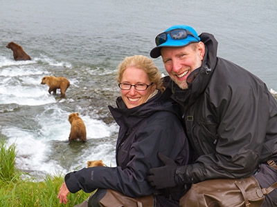 Couple posing in front of a group of bears playing in the water